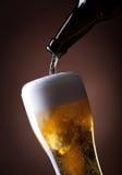 Ölexponeringsglas och flaska på en brown Royaltyfri Bild