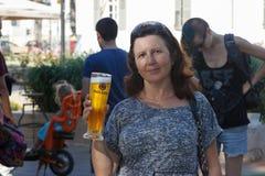 Ölfestivalbesökaren poserar med ett exponeringsglas av öl Fotografering för Bildbyråer