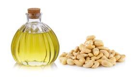 Ölflasche und Acajounuss auf weißem Hintergrund Stockfotografie