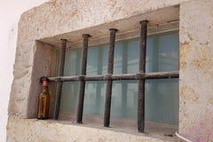 Ölflaska framme av det rostiga gallerförsedda fönstret Arkivfoto