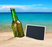 Ölflaska i sanden på stranden och en svart tavla Arkivbild