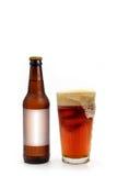 Ölflaska med vitmellanrumsetiketten och flödande över ölexponeringsglas Arkivfoto