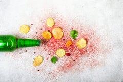 Ölflaska och frasiga potatischiper på en grå bakgrund Royaltyfri Foto