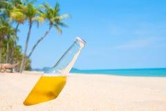 Ölflaska på en sandig strand Fotografering för Bildbyråer