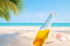 Ölflaska på en sandig strand med palmträdet Royaltyfria Foton