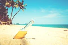 Ölflaska på en sandig strand med palmträdet Arkivfoton