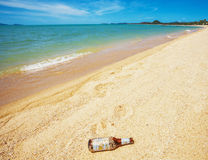 Ölflaska på stranden Arkivbild