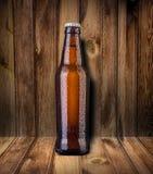 Ölflaska på träbakgrund Arkivfoto