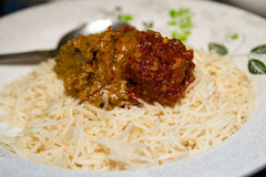 Öliger sahniger Reis auf einer Platte mit Rindfleischcurry stockfotografie