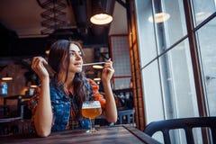 Ölkvinna som tycker om ett nytt utkast på kafét Bearbeta för konst Arkivbilder
