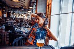 Ölkvinna som tycker om ett nytt utkast på kafét Bearbeta för konst Arkivfoto