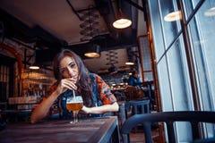 Ölkvinna som tycker om ett nytt utkast på kafét Bearbeta för konst Royaltyfri Bild