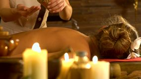Ölmassage, die in Hände gießt Frau, die auf hölzernem Massagebadekurortbett liegt Langsame Bewegung stock video