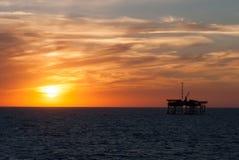 Ölplattform und Sonnenuntergang Stockbild