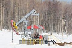 Ölpumpe auf Holz- und Schneehintergrund Stockfotografie