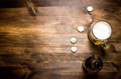 Ölstil - flaska, öl i exponeringsglaset och räkningar på trätabellen Fritt avstånd för text Royaltyfri Bild