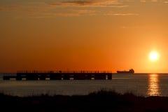 Öltanker und Pier am Sonnenaufgang Stockbilder