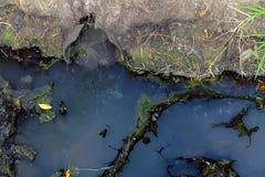 Ölteppich und schmutziger Wasserstrom aus dem Abwasserkanal, der Verschmutzung und dem en heraus Stockfoto