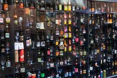 Ölvägg i den Bruges stången med olika flaskor och exponeringsglas Royaltyfri Bild
