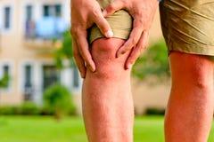 Öm knä för maninnehavhand Fotografering för Bildbyråer