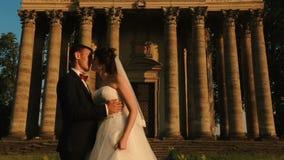 Ömt kyssa par av attraktiva lyckliga nygifta personer över bakgrunden av gammal barock stilbyggnad under stock video