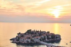 Ön av Sveti Stefan Semesterorten av Montenegro Solnedgång på ön av Sveti Stefan royaltyfri bild