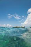 Ön med gömma i handflatan i havet Arkivfoto