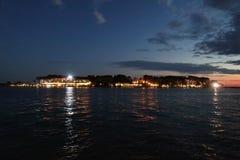 Ön på natten med ljus reflekterade i havet Royaltyfri Bild