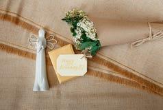Önskakort på den guld- närvarande asken med den vita keramiska ängeln Vita små blommor för bukett i brunt hantverkpapper med rad  Arkivbild
