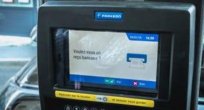 Önskar du ett bankkvitto som är skriftligt i franskt på en maskin för parkera biljett royaltyfria foton