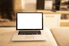 Öppen aluminiumbärbar dator med den tomma skärmen för kopieringsutrymme på en soffaottoman i selektiv fokus med skuggad vardagsru arkivbilder