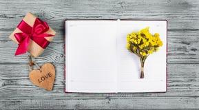 Öppen anteckningsbok, blommor och ask med gåvan kopiera avstånd Det pappers- hålet rev sönder i hjärta Shape med gammal Wood bakg royaltyfria foton