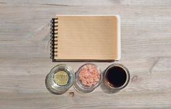 Öppen anteckningsbok för mellanrum för anmärkningar, salt, olje- och sås på en trätabell Arkivbild