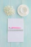 Öppen anteckningsbok med den rosa färgpennan, coffeecup och vanliga hortensian Royaltyfri Foto