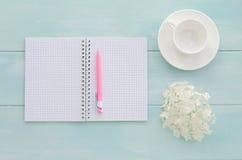 Öppen anteckningsbok med den rosa färgpennan, coffeecup och vanliga hortensian Royaltyfri Fotografi