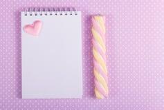 Öppen anteckningsbok med en tom sida, en marshmallowpinne och en liten valentin på en bakgrund av pricken Arkivfoton