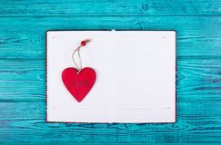 Öppen anteckningsbok med rengöringsidor och en röd hjärta Mallar och bakgrunder Royaltyfri Fotografi