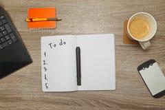 Öppen anteckningsbok med text` som GÖR ` och en kopp kaffe på träbakgrund Arkivbild