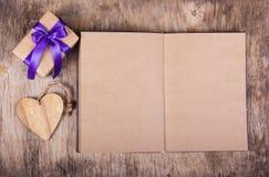 Öppen anteckningsbok med tomma sidor Boxas med en gåva och en valentin på den gamla träbakgrunden valentin för dag s kopiera avst Arkivbild
