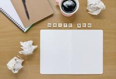 Öppen anteckningsbok- och kaffekopp på ett författareskrivbord, med tegelplattor som ut stavar 'för att skriva nu ', arkivfoton