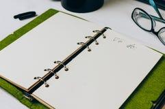 Öppen anteckningsbok på tabellen av vit färg royaltyfria bilder