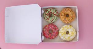 Öppen ask för kvinnlig hand med färgrika donuts på rosa färger stock video