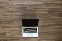 Öppen bärbar dator med den isolerade skärmen på det gamla träskrivbordet Arkivfoto