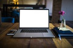Öppen bärbar datordator med den vita tomma skärmen med kopieringsutrymme för annonsering av textmeddelandet som ligger på en trät arkivfoto