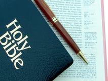Öppen bibel för grek med pennan Arkivfoton