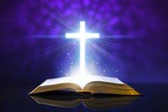 Öppen bibel på ett glass skrivbord med glöda argt Royaltyfri Bild