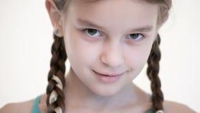 Öppen blick för närbild av en Caucasian flicka med råttsvansar som öppnar och stänger hennes ögon Ilsket och blint i kameran lager videofilmer