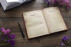 Öppen bok, blommor och penna arkivbild