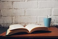 Öppen bok bredvid en kaffekopp arkivfoto