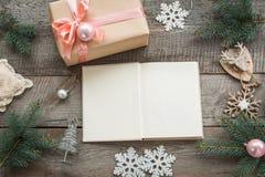 Öppen bok för dig julönska Förberedelse för julferie 1 livstid fortfarande Julgåvaask med det rosa bandet och omkring Arkivbilder